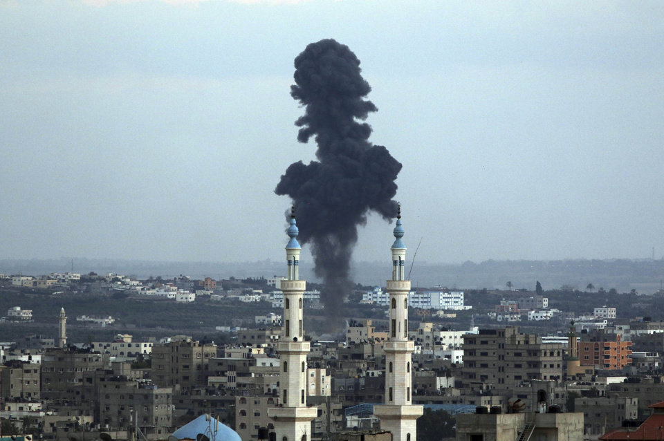 Photo - Smoke rises behind a mosque's minarets after an Israeli missile strike in Gaza City, northern Gaza Strip, Friday, July 18, 2014. Israeli troops pushed deeper into Gaza on Friday to destroy rocket launching sites and tunnels, firing volleys of tank shells and clashing with Palestinian fighters in a high-stakes ground offensive meant to weaken the enclave's Hamas rulers. (AP Photo/Hatem Moussa)
