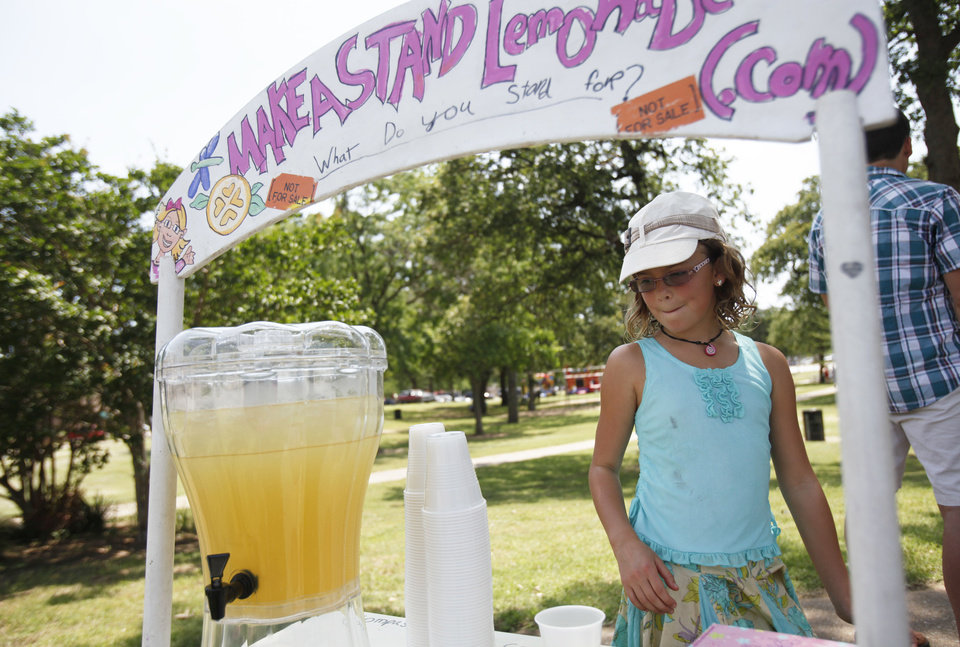 Photo - Vivienne Harr, 9, of Fairfax, Calif., works at her Make A Stand lemonade stand Friday in Woodland Park in Shawnee. Photo by Aliki Dyer, The Oklahoman  Aliki Dyer - The Oklahoman