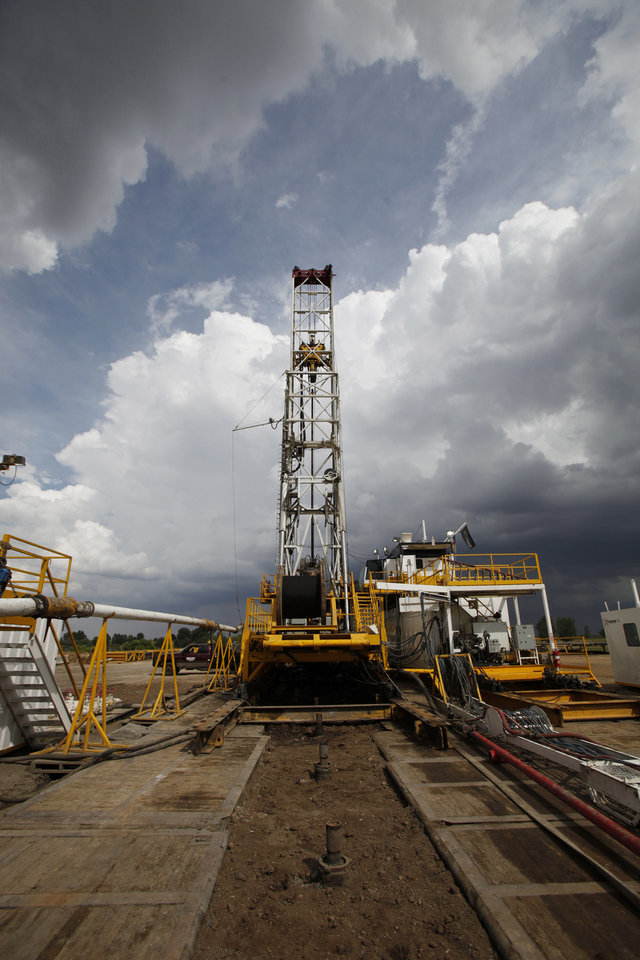 """Photo - FILE - This Tuesday, Aug. 25, 2009 file photo shows capped wells in the foreground as Anadarko Petroleum Corp., uses a walking rig to drill a series of wells on a pad on a Weld County farm near Mead, Colo. In the past, when rigs were finished drilling a well, they had to be disassembled and trucked to the next location, a process that took several days. Now some rigs can """"walk"""" hundreds of feet on hydraulic shoes to the next drilling spot. This reduces drilling costs. (AP Photo/Ed Andrieski, File)"""