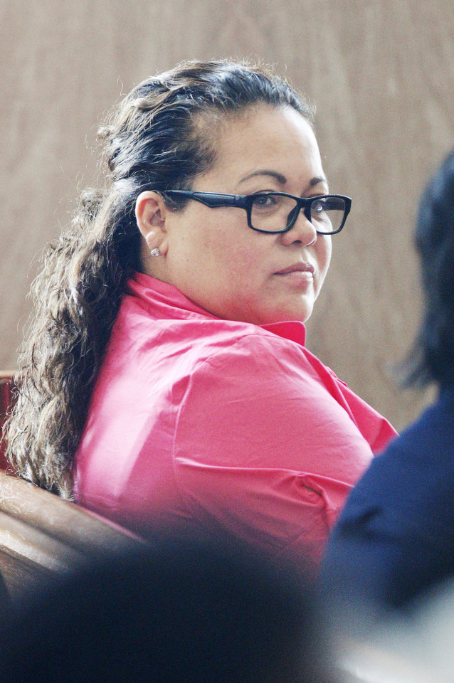 Photo - Elizabeth Hinojosa, of Jourdanton, Texas, sits in the courtroom while waiting to plead guilty Wednesday at the Oklahoma County Courthouse. Hinojosa, a dental assistant and her daughter, a dental receptionist, both pleaded guilty to practicing dentistry without a license. Photo by Paul B. Southerland, The Oklahoman  PAUL B. SOUTHERLAND - PAUL B. SOUTHERLAND