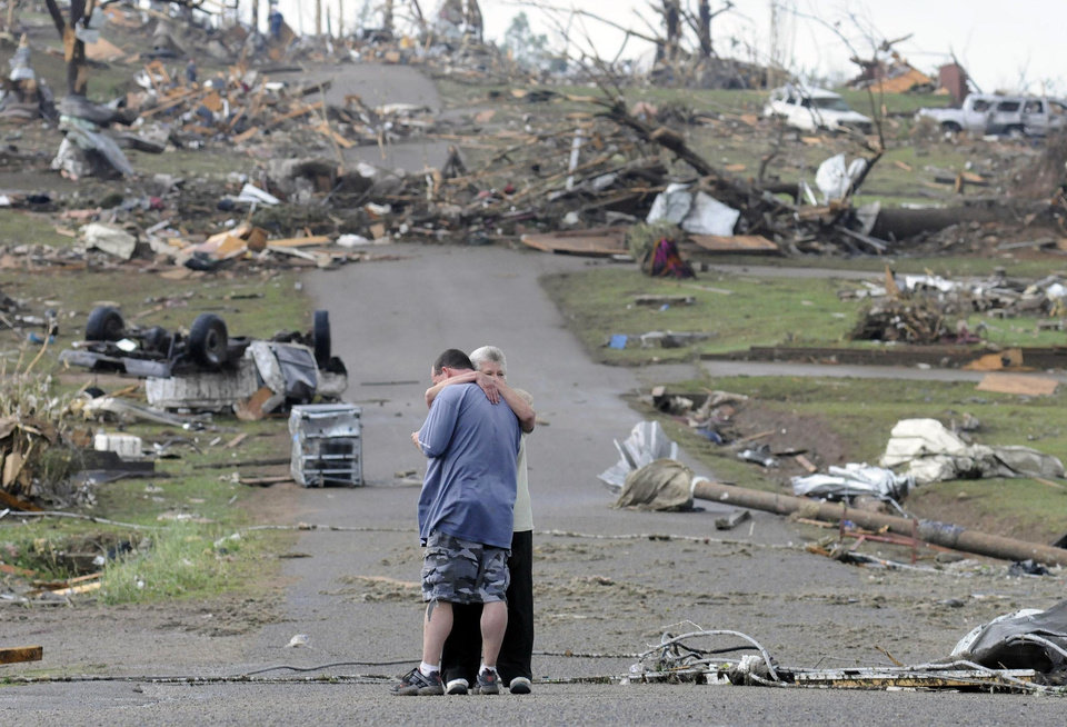 Photo - Michael Dunn is hugged by his mother Patricia Dunn as they stand in the road that lead to his house which was completely destroyed after a tornado touched down, Wednesday, April 27, 2011 in Concord, Ala. (AP Photo/Birmingham News, Jeff Roberts)