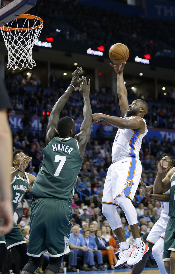 Photo -  Oklahoma City's Raymond Felton goes for a layup as Milwaukee's Thon Maker defends during Friday's game.  [Photo by Sarah Phipps, The Oklahoman]