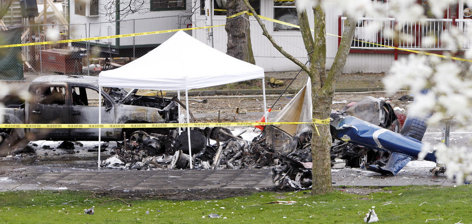 Photo - Caution tape surrounds the charred wreckage of a news helicopter and two vehicles after the chopper crashed into a city street near the Space Needle, Tuesday, March 18, 2014, in Seattle. Two people were killed and another critically injured. (AP Photo/Stephen Brashear)