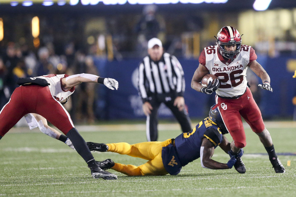 Photo - Oklahoma Sooners running back Kennedy Brooks (26) runs through an attempted tackle by West Virginia Mountaineers defensive lineman Ezekiel Rose (5) during the NCAA football game between the Oklahoma Sooners and the West Virginia Mountaineers at Mountaineer Field at Milan Puskar Stadium in Morgantown, W.Va on Friday, November 23, 2018. IAN MAULE/Tulsa World