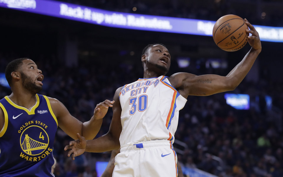 Photo - Oklahoma City Thunder guard Deonte Burton, right, rebounds the ball from Golden State Warriors' Omari Spellman (4) in the first half of an NBA basketball game Monday, Nov. 25, 2019, in San Francisco. (AP Photo/Ben Margot)