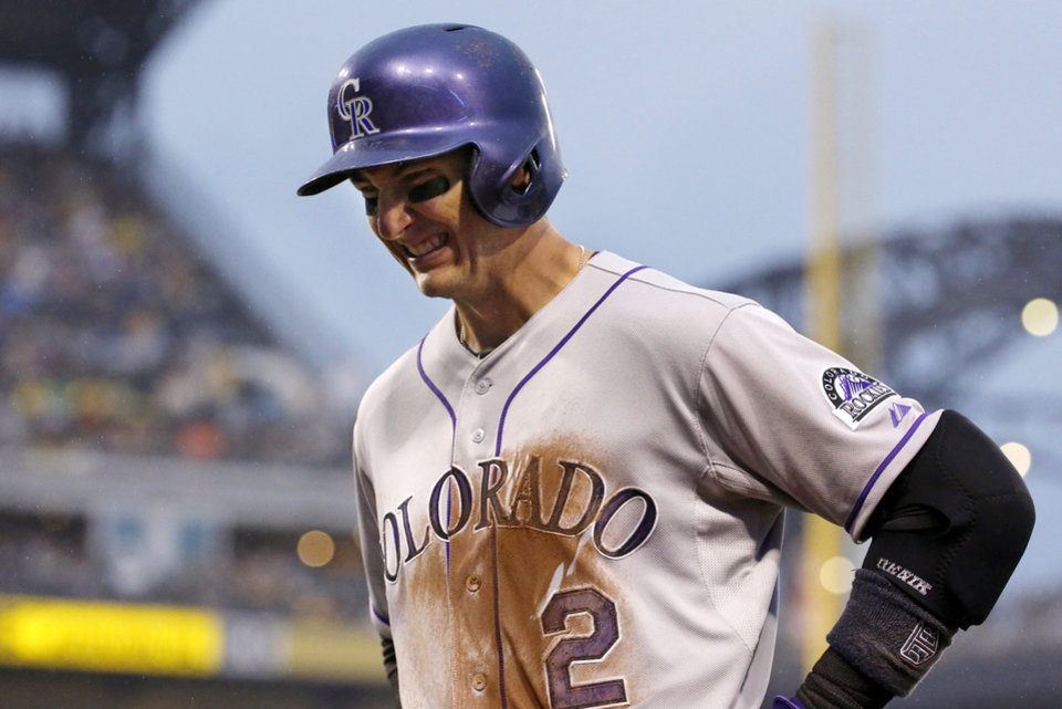 Photo - Colorado Rockies shortstop Troy Tulowitzki (2) grimaces as he walks back to the dugout after grounding out to end the fourth inning of a baseball game against the Pittsburgh Pirates in Pittsburgh Saturday, July 19, 2014. Tulowitzki left the game.(AP Photo/Gene J. Puskar)