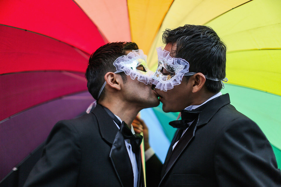 Photo - Men kiss under a rainbow umbrella during a gay pride parade in Lima, Peru, Saturday, June 28, 2014. Gays, lesbians and transgenders are holding gay pride parades worldwide this month as part of annual demonstrations demanding equal rights and to protest discrimination. (AP Photo/Sebastian Castaneda)