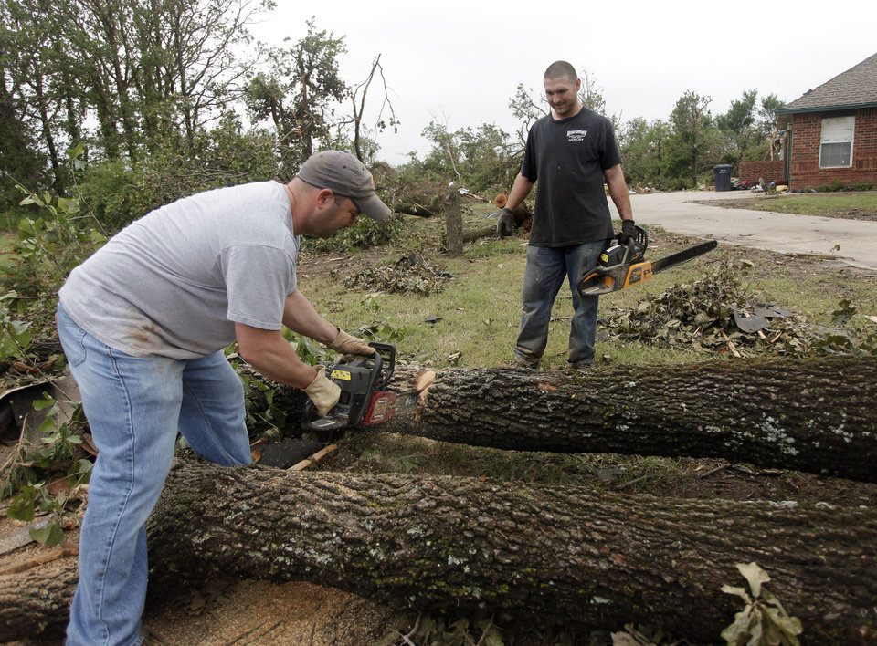 Photo - Dustin Moss, left, and Rory Farmer use chain saws to cut up damaged trees in the Dripping Springs Estates Saturday, May 15, 2010. Saturday hundreds of volunteers went into areas that had been affected by last week's tornadoes to help clear debris. Photo by Doug Hoke, The Oklahoman.