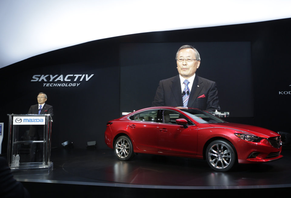Photo - Mazda CEO Takashi Yamanouchi speaks while the Mazda6 is shown during it's North American debut at the LA Auto Show in Los Angeles, Thursday, Nov. 29, 2012. (AP Photo/Chris Carlson)
