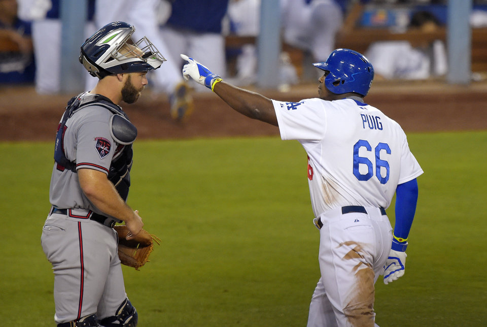 Photo - Los Angeles Dodgers' Yasiel Puig, right gestures after hitting a solo home run, next to Atlanta Braves catcher Evan Gattis during the third inning of a baseball game, Thursday, July 31, 2014, in Los Angeles. (AP Photo/Mark J. Terrill)