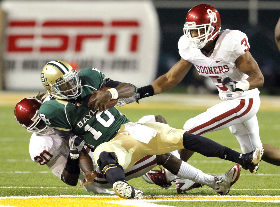 Photo - Quinton Carter (20) takes down Baylor Quarterback Robert Grffin III during the second half of the college football game between the University of Oklahoma Sooners (OU) and the Baylor Bears (BU) at Floyd Casey Stadium on Saturday, November 20, 2010, in Waco, Texas.   Photo by Steve Sisney, The Oklahoman