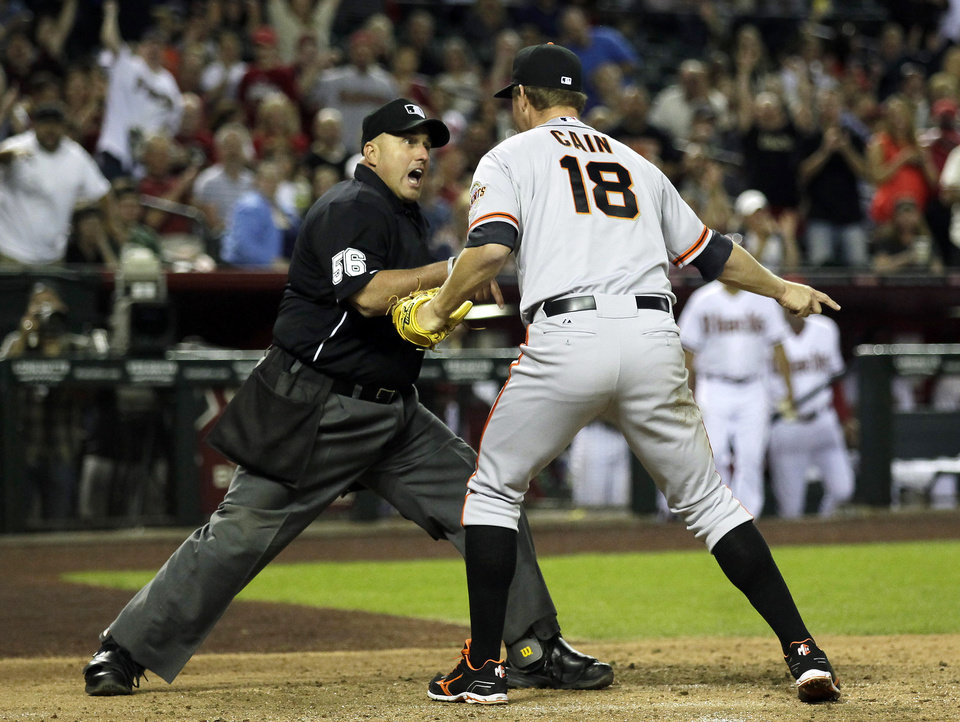 Photo - San Francisco Giants starting pitcher Matt Cain (18) talks to home plate umpire Eric Cooper (56) after Cain thought he tagged out a runner at home in the fourth inning during a baseball game, Tuesday, April 1, 2014, in Phoenix. (AP Photo/Rick Scuteri)