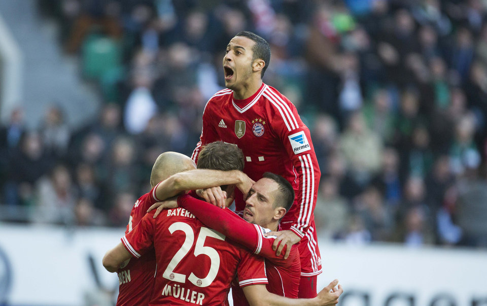 Photo - Bayern's Thiago Alcantara of Spain, top, Bayern's Arjen Robben of the Netherlands, Bayern's Thomas Mueller, and Bayern's Franck Ribery of France, bottom from left, celebrate after Mueller scored his side's 2nd goal during the German Bundesliga soccer match between VfL Wolfsburg and Bayern Munich in Wolfsburg, Germany, Saturday, March 8, 2014. (AP Photo/Gero Breloer)