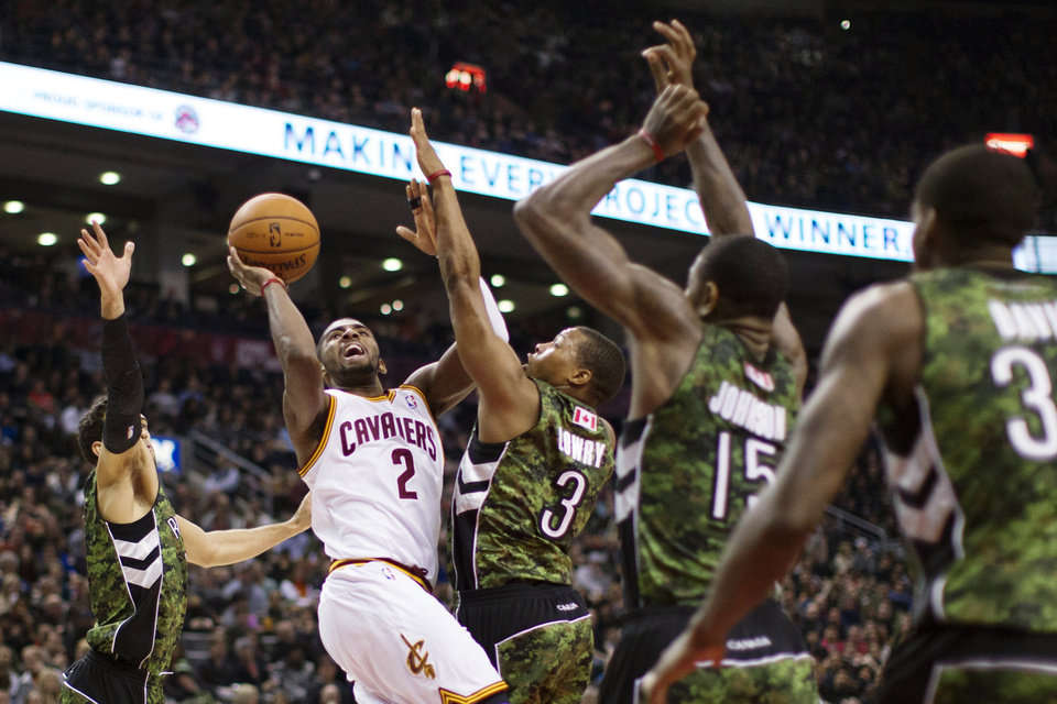 Cleveland Cavaliers\' Kyrie Irving (2) shoots against Toronto Raptors\' Landry Fields, left, Kyle Lowry (3), Amir Johnson (15) and Ed Davis (32) during the first half of an NBA basketball game, Saturday, Jan. 26, 2013, in Toronto. (AP Photo/The Canadian Press, Chris Young)