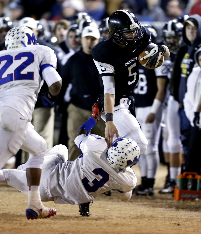 Photo - Meeker's Jake Sandlee runs around end and is tackled by Cameron Batson as the Millwood Falcons play the Meeker Bulldogs in state high school football playoffs on Friday, Nov. 29, 2013, in Meeker, Okla.  Photo by Steve Sisney, The Oklahoman