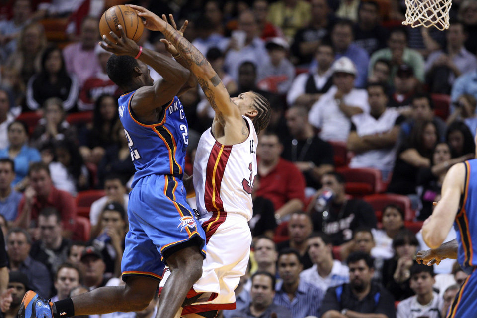 Miami Heat's Michael Beasley (30) tries to block a shot by Oklahoma City  Thunder's Jeff Green (22) during second half of a NBA basketball game in Miami, Tuesday, Nov. 17, 2009. The  Thunder won 100-87. (AP Photo/J Pat Carter)