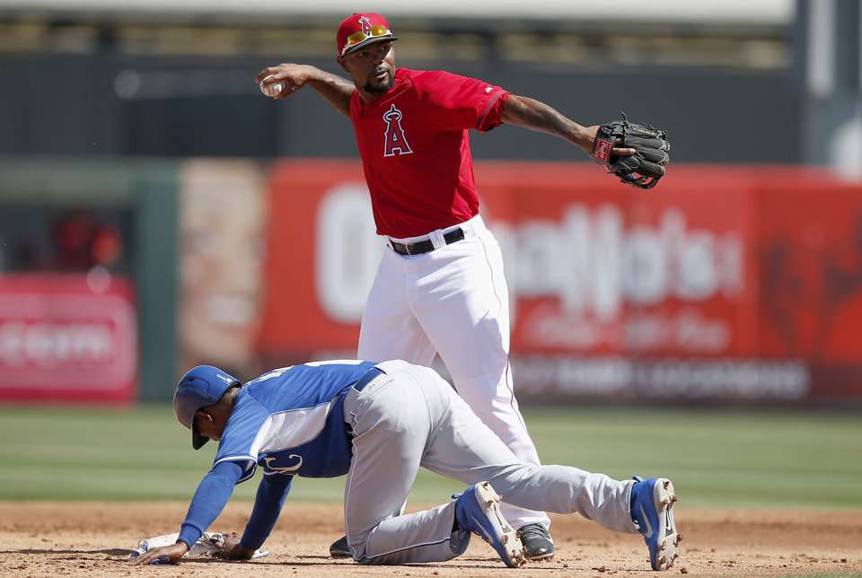 Photo - Los Angeles Angels' Howie Kendrick, top, throws the ball back to the pitcher after Kansas City Royals' Jarrod Dyson, left, dove safely back into second base during the second inning of a spring training baseball game Friday, March 21, 2014, in Tempe, Ariz. (AP Photo/Ross D. Franklin)
