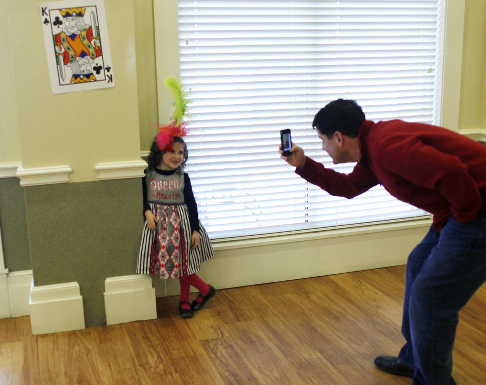 Photo - Craig Brown photographs his daughter, Maggie, 5, and her fancy hat at the Daddy-Daughter Mad Hatter Tea Party in Edmond. PHOTO BY DOUG HOKE, THE OKLAHOMAN.  Doug Hoke - THE OKLAHOMAN