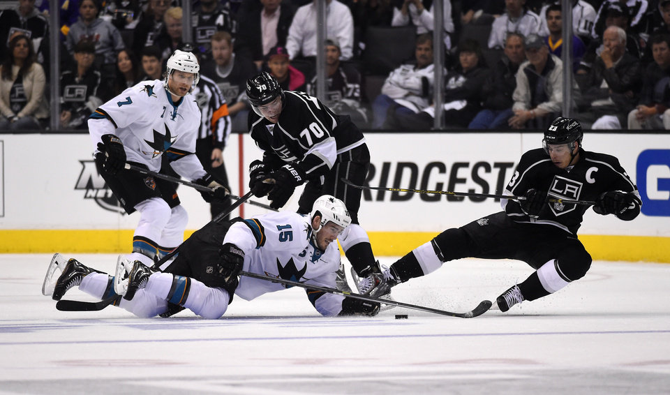 Photo - San Jose Sharks left wing James Sheppard, lower left, battles for the puck with Los Angeles Kings right wing Dustin Brown, right, as defenseman Brad Stuart, upper left, and left wing Tanner Pearson look on during the first period in Game 3 of an NHL hockey first-round playoff series, Tuesday, April 22, 2014, in Los Angeles. (AP Photo/Mark J. Terrill)