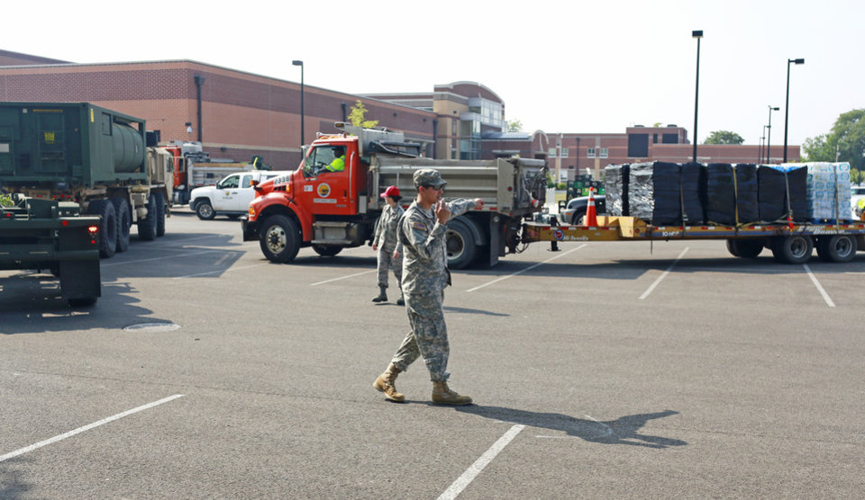 Photo - Ohio Army National Guard Spc. Luis Cardenas directs military vehicles carrying fresh drinking water, Sunday, Aug. 3, 2014, at Woodward High School in Toledo, Ohio. More tests are needed to ensure that toxins are out of Toledo's water supply, the mayor said Sunday, instructing the 400,000 people in the region to avoid drinking tap water for a second day. Toledo officials issued the warning early Saturday after tests at one treatment plant showed two sample readings for microsystin above the standard for consumption, possibly because of algae on Lake Erie. (AP Photo/Haraz N. Ghanbari)
