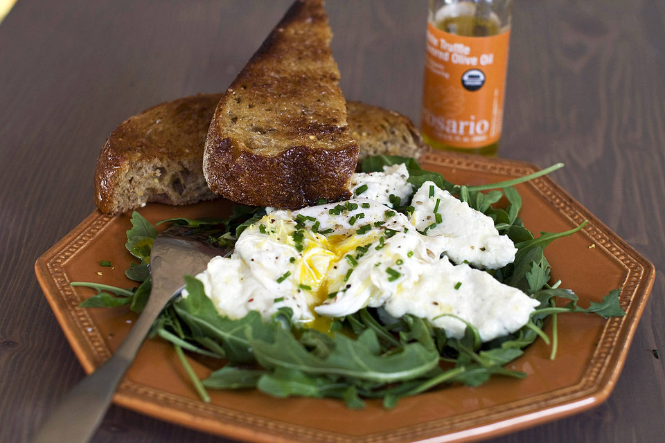 Poached eggs over ricotta cheese on arugula with sliced toast. MATTHEW MEAD - AP
