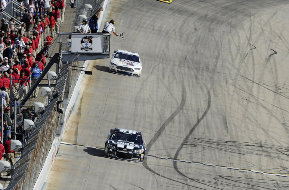 Photo - Jimmie Johnson takes the checkered flag to win the NASCAR Sprint Cup series auto race, Sunday, June 1, 2014, at Dover International Speedway in Dover, Del. Behind him is Brad Keselowski. (AP Photo/Nick Wass)