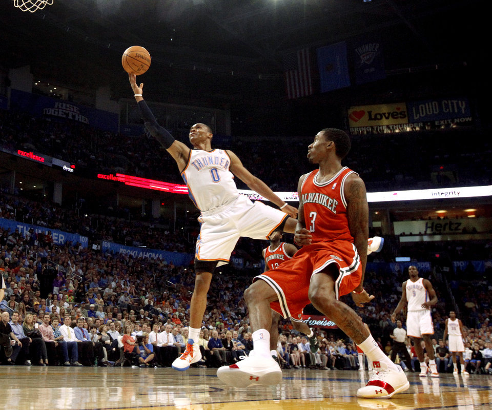 Photo - Oklahoma City's Russell Westbrook (0) goes past Milwaukee's Brandon Jennings (3) during the NBA basketball game between the Oklahoma City Thunder and the Milwaukee Bucks at the Oklahoma City Arena, Wednesday, April 13, 2011. Photo by Bryan Terry, The Oklahoman