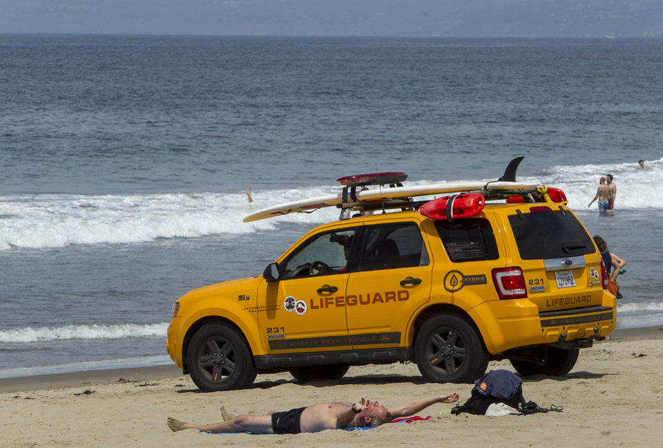 Photo - A beachgoer enjoys the sun next to a parked Los Angeles County Fire Department Lifeguard vehicle at Venice Beach in Los Angeles Monday, July 28, 2014. Los Angeles' popular Venice Beach teemed with people enjoying a weekend outing on the boardwalk and sand when lifeguards and other witnesses say lightning from a rare summer thunderstorm hit without warning, injuring or rattling more than a dozen people and leaving a 21-year-old man dead. The witnesses said the strike hit with a tremendous boom about 2:30 p.m. Sunday, July 27, rattling buildings and showering a lifeguard headquarters with sparks. (AP Photo/Damian Dovarganes)