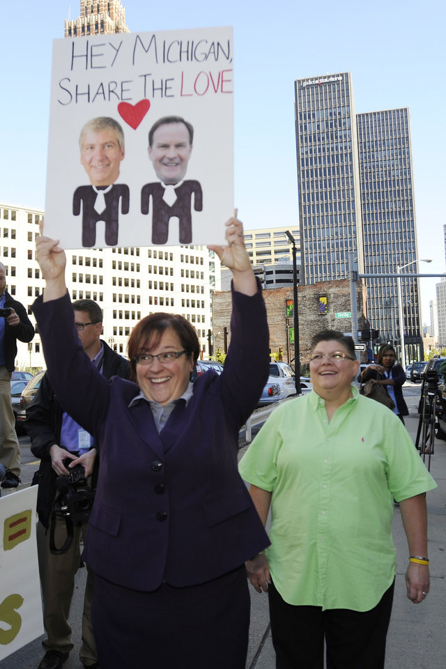 Photo - April DeBoer, left, and Jayne Rowse  protest at the federal courthouse in Detroit on Wednesday, Oct. 16, 2013. The protest is in support of a federal lawsuit involving same-sex couple DeBoer and Rowse who are seeking to overturn Michigan's ban on gay adoption and same-sex marriage.    (AP Photo/Detroit News, David Coates)  DETROIT FREE PRESS OUT; HUFFINGTON POST OUT