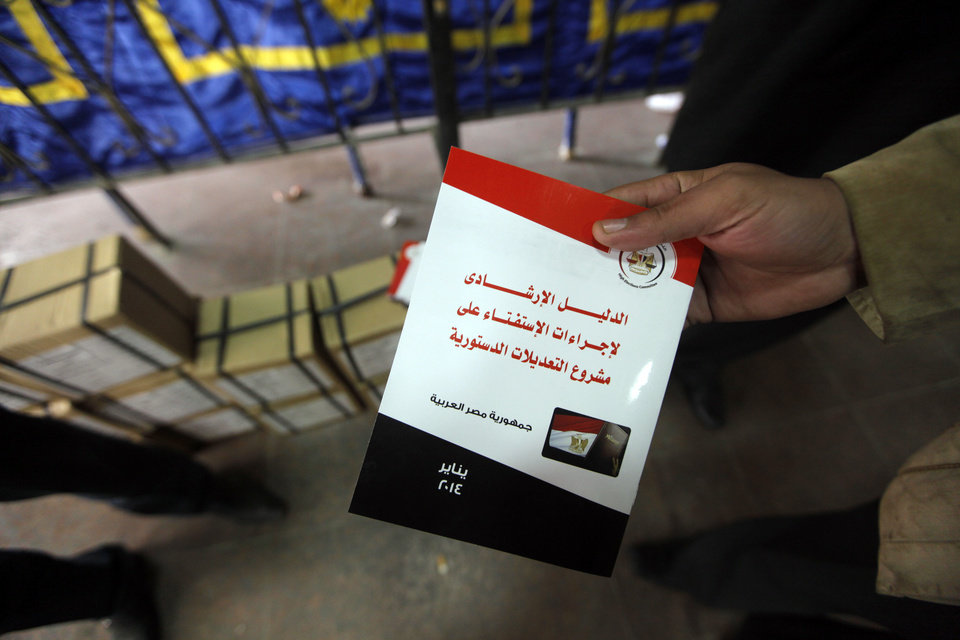 Photo - An Egyptian election worker displays a guide book for voting in the country's constitutional referendum, at the Giza courthouse, in Cairo, Egypt, Monday, Jan. 13, 2014. The January 14-15 vote on the draft constitution will be the first real test of the post-Morsi regime. A comfortable