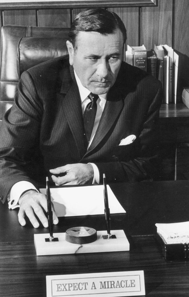 Photo - Oral Roberts, Tulsa, Ok. evangelist and founder of Oral Roberts University, at his desk behind the motto
