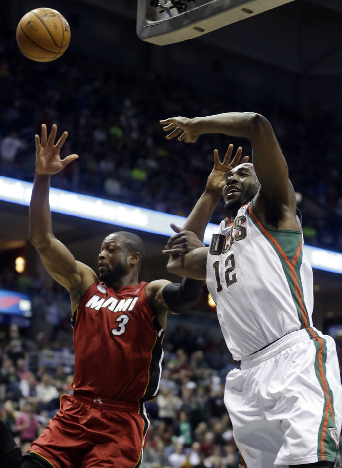 Photo - Miami Heat's Dwyane Wade, left, knocks the ball away from Milwaukee Bucks' Luc Richard Mbah a Moute (12) during the second half of Game 3 in their first-round NBA basketball playoff series on Thursday, April 25, 2013, in Milwaukee. (AP Photo/Morry Gash)