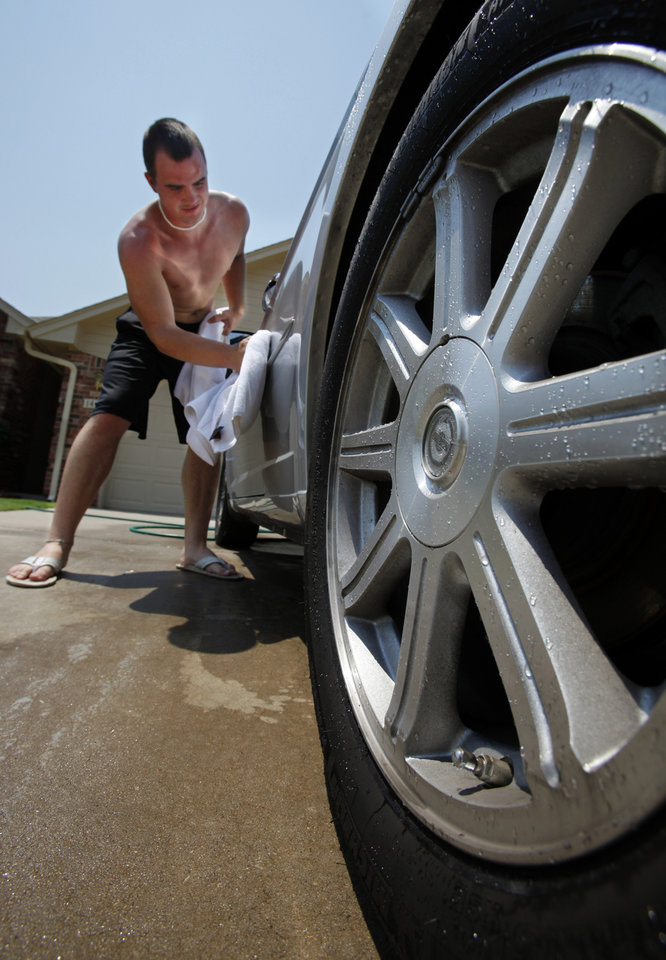 Evan Fields keeps his house at 85 degrees in the afternoon to conserve energy so outside is not so unattractive as he washes the car at 2 p.m. with the temperature topping 100 degrees for the second day in a row on Wednesday, June 27, 2012, in Norman, Okla. Photo by Steve Sisney, The Oklahoman