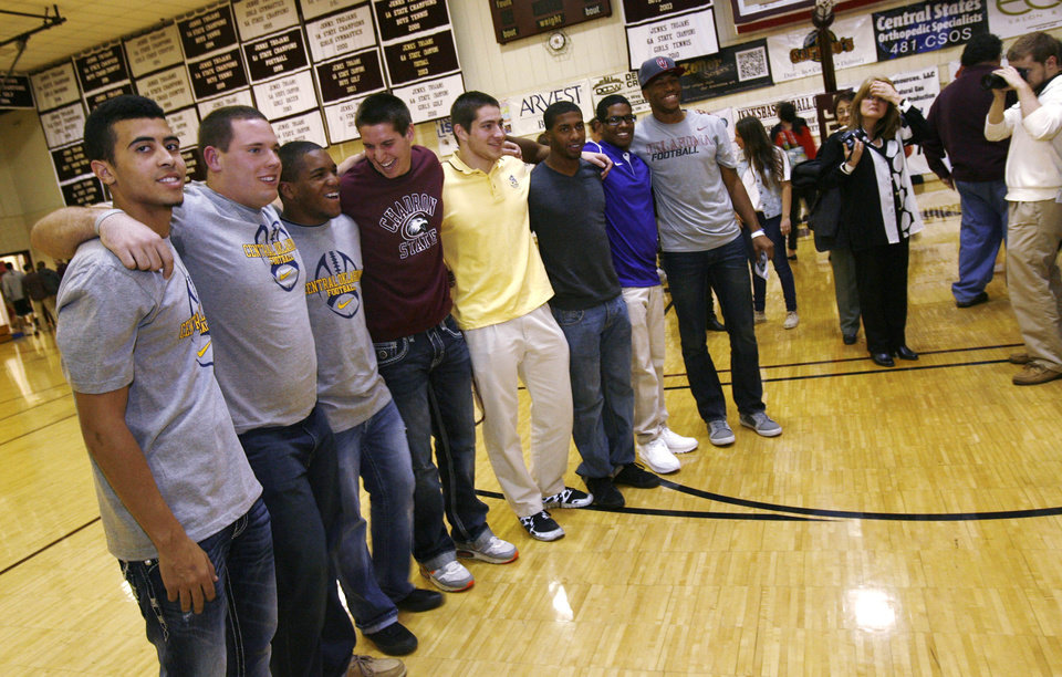Photo - Members of the Jenks high school football team including Taylor Hunter (left), Brandon Waggoner, Braden Calip, Garrett Patterson, Nick Lucido, Trey'vonne Barre, Jeff Scallion, and Jordan Smallwood pose for a photo for family and friends during signing day in Jenks, Okla., on February 6,2013. JAMES GIBBARD/Tulsa World