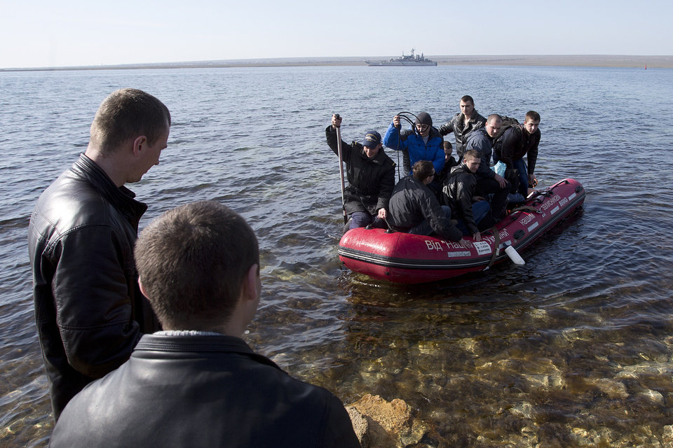 Photo - Ukrainian sailors leave the Konstantin Olshansky navy ship in the bay of Donuzlav, Crimea, Monday, March 24, 2014. Ukraine's fledgling government ordered troops to retreat from Crimea on Monday, ending days of wavering as Western leaders tried to present a unified response to Russia's increasingly firm control of the peninsula. Tired of weeks of tensions and uncertainty and Kiev's indecision, some Ukrainian troops were leaving their bases. In the bay of Donuzlav in western Crimea, the crew of the Ukrainian navy ship Konstantin Olshanskiy were packing up and leaving Monday. (AP Photo/Pavel Golovkin)