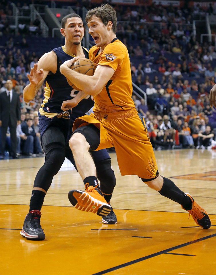Photo - Phoenix Suns' Goran Dragic, of Slovenia, drives past New Orleans Pelicans' Eric Gordan during the second half of an NBA basketball game, Friday, Feb. 28, 2014, in Phoenix. The Suns won 116-104. (AP Photo/Matt York)