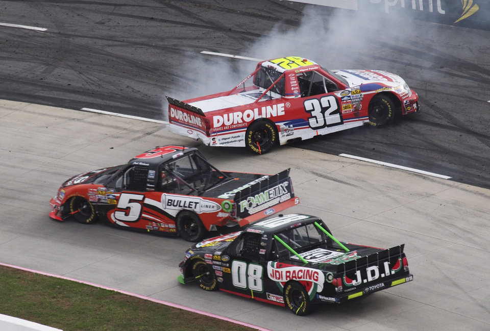 Photo -   Miguel Paludo (32) spins out in front of Josh Richards (5) and Ross Chastain (08) during the NASCAR truck race at the Martinsville Speedway in Martinsville, Va. Saturday, Oct. 27, 2012. (AP Photo/Steve Sheppard)