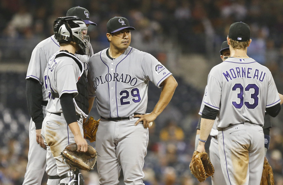 Photo - Colorado Rockies starting pitcher Jorge De La Rosa, center, gets a visit from catcher Jordan Pacheco and pitching coach Jim Wright in the fifth inning of a baseball game Wednesday, April 16, 2014, in San Diego.  (AP Photo/Lenny Ignelzi)