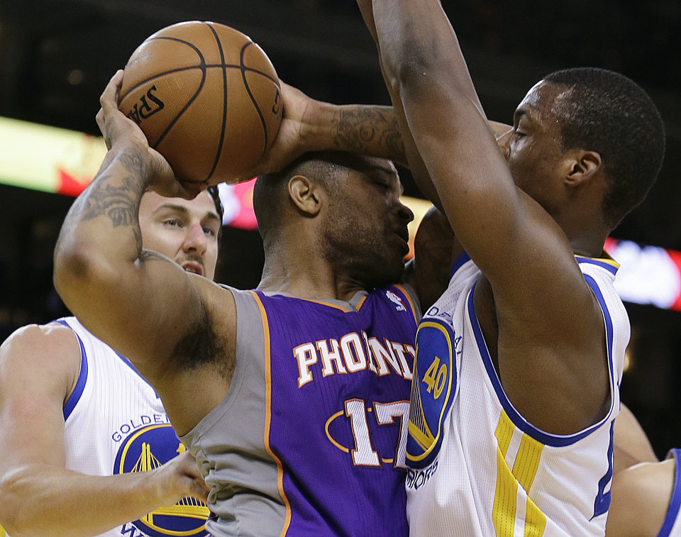 Phoenix Sun's P.J. Tucker, center, looks to pass away from Golden State Warriors' Harrison Barnes, right, and Andrew Bogut during the first half of an NBA basketball game, Wednesday, Feb. 20, 2013, in Oakland, Calif. (AP Photo/Ben Margot)
