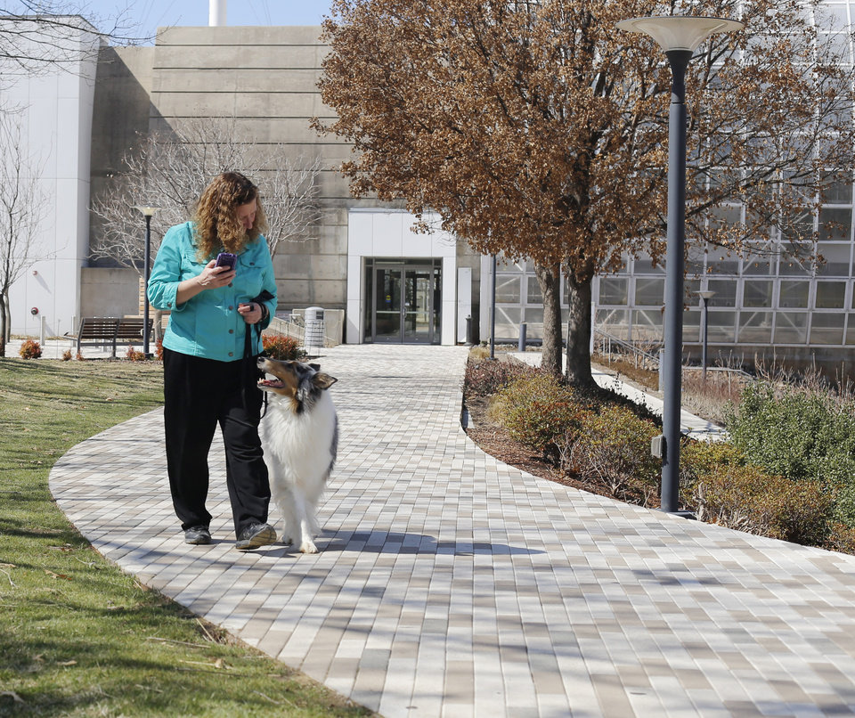 Photo - Connie Sutter, from Carol, Michighan, walks her rough blue merle collie Fiona in the Myriad Botanical Gardens. Sutter is in town at the Collie Club of America dog show at the Cox Convention Center in  Oklahoma City, Wednesday, March 11, 2015. Photo by Doug Hoke, The Oklahoman