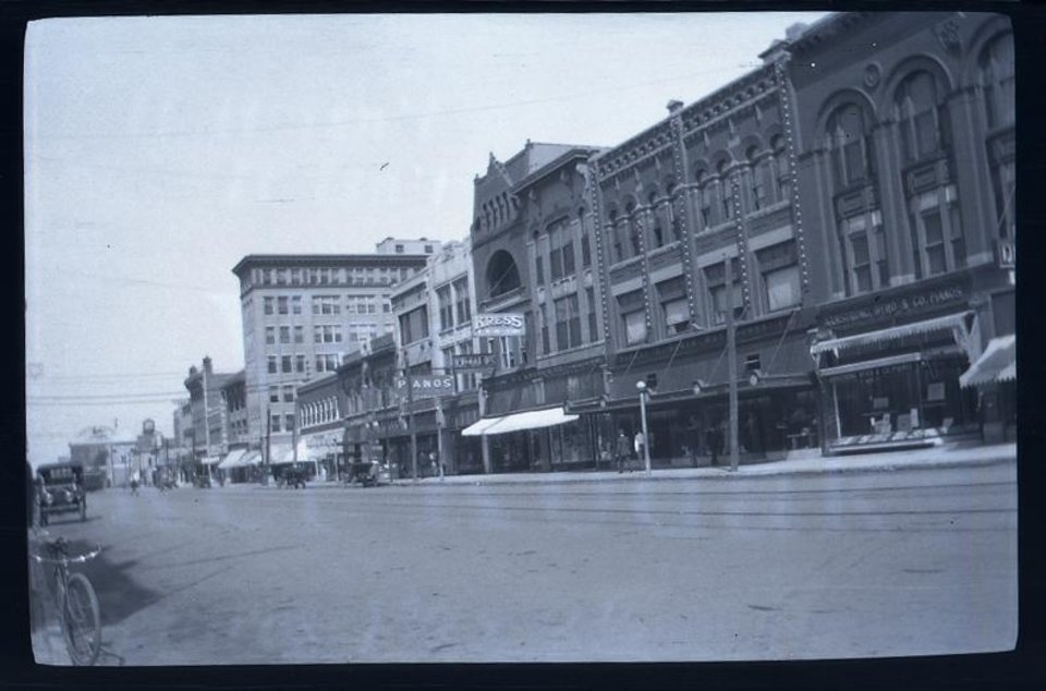 Photo -  This shot of Main Street in 1913 includes a stretch of buildings that later became home to the home of John A. Brown's Department Store. The buildings were torn down in the mid-1970s as part of the Urban Renewal Pei Plan. Photo provided by the Oklahoma Historical Society.