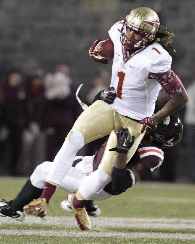 Photo -   Florida State wide receiver Kelvin Benjamin (1) is brought down by Virginia Tech cornerback Antone Exum (1) during the first half of an NCAA college football game in Blacksburg, Va., Thursday, Nov. 8, 2012. (AP Photo/Steve Helber)