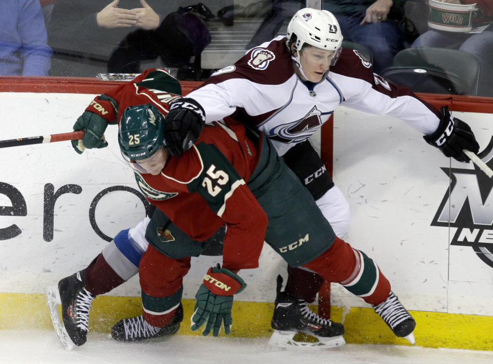 Photo - Colorado Avalanche's Nathan MacKinnon, right, and Minnesota Wild's Jonas Brodin, of Sweden, gets tangled up along the boards in the first period of an NHL hockey game, Saturday, Jan. 11, 2014, in St. Paul, Minn. (AP Photo/Jim Mone)