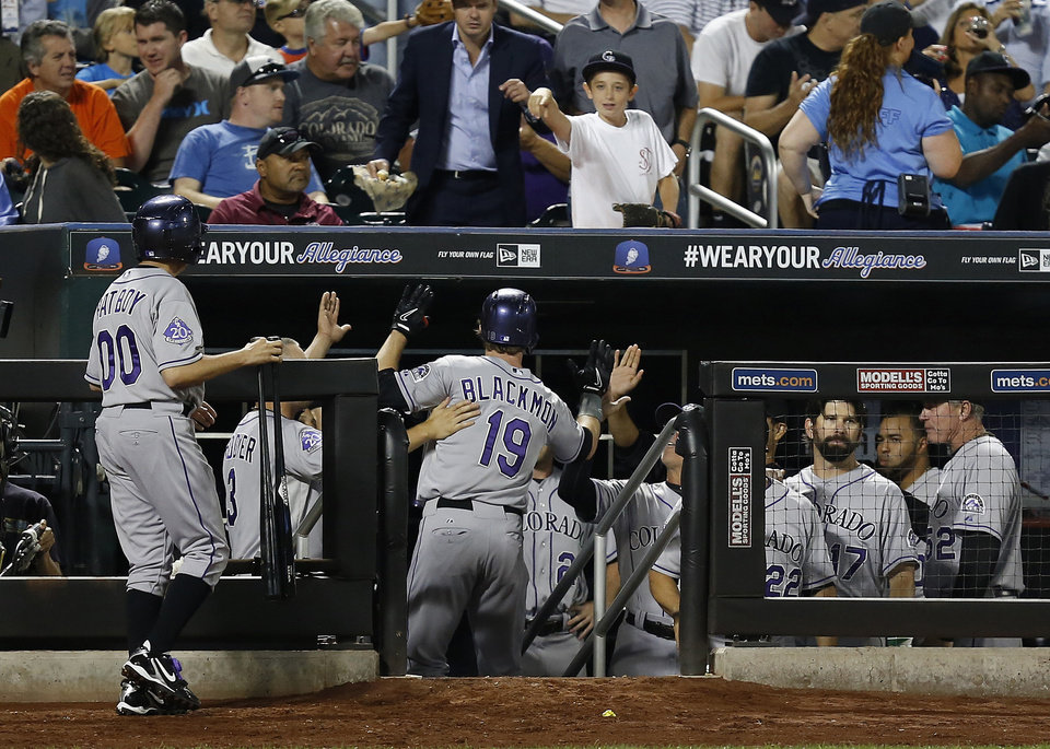 Photo - Colorado Rockies' Charlie Blackmon (19) celebrates with his teammates after hitting a solo home run in the sixth inning of a baseball game against the New York Mets at Citi Field, Tuesday, Aug. 6, 2013, in New York. (AP Photo/John Minchillo)