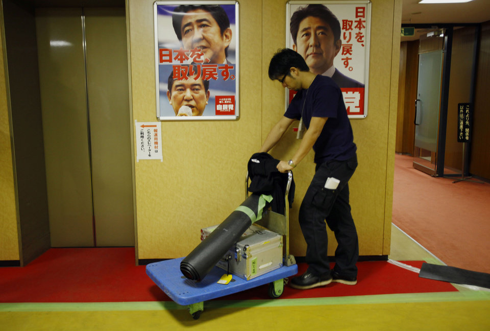 A TV crew member delivers equipments in preparation of live coverage of Japan's parliamentary elections at Liberal Democratic Party headquarters in Tokyo, Sunday, Dec. 16, 2012. Japanese voted Sunday in parliamentary elections that were expected to put the once-dominant conservatives back in power after a three-year break, and bring in a more nationalistic government amid tensions with big neighbor China. (AP Photo/Junji Kurokawa)