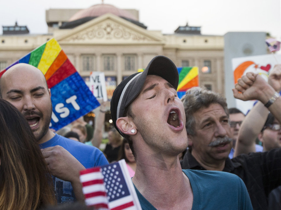 Photo - Demonstrators including Christopher Bullock, center, celebrate after hearing that Arizona Gov. Jan Brewer was going to veto SB1062, Wednesday, Feb. 26, 2014, in Phoenix. The bill is designed to give added protection from lawsuits to people who assert their religious beliefs in refusing service to gays. (AP Photo/The Arizona Republic, Pat Shannahan) MARICOPA COUNTY OUT; MAGS OUT; NO SALES.