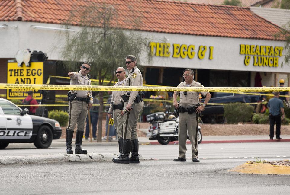 Photo - Las Vegas Metro police officers examine the scene of an accident where a vehicle crashed into a crowded restaurant, Monday, April 1, 2013, in Las Vegas. Ten people were seriously injured and at least one person was arrested Monday after the car plowed into the patio of the Egg & I restaurant during the lunch hour and came to rest with its hood inside a shattered plate glass window. Victims were transported to two nearby hospitals with non-life threatening injuries after the crash shortly after 12:30 p.m. (AP Photo/Julie Jacobson)