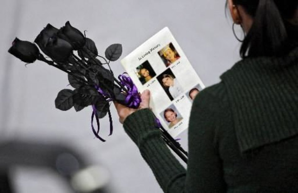 Photo - A mourner holds black roses and a funeral program during services for Autumn Rust and her four children in this Jan. 21 photo by Chris Landsberger.