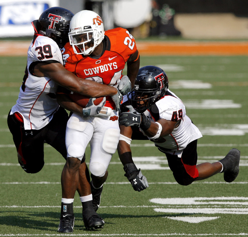 Photo - OSU's Kendall Hunter (24) drags Texas Tech defenders Marlon Williams (39) and Joe Garcia during the second half of the college football game between the Oklahoma State University Cowboys (OSU) and the Texas Tech University Red Raiders (TTU) at Boone Pickens Stadium  on Saturday, Sept. 22, 2007, in Stillwater, Okla.   By MATT STRASEN, The Oklahoman  ORG XMIT: KOD
