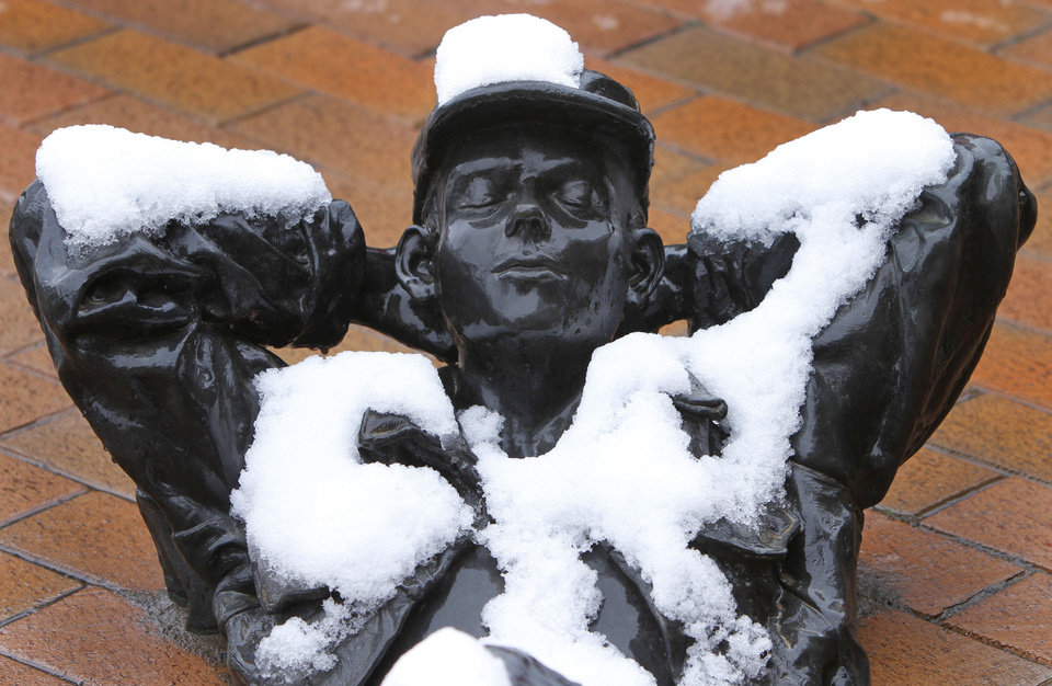Snow on Wednesday blankets the �Pastoral Dreamer,� a bronze statue between Main Street and First Street on Broadway in Edmond. PHOTOS BY STEVE GOOCH, THE OKLAHOMAN